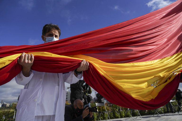 El jefe de la UCI del hospital Infanta Sofía sostiene la bandera de 75 metros cuadrados izada este viernes en Valdebebas.