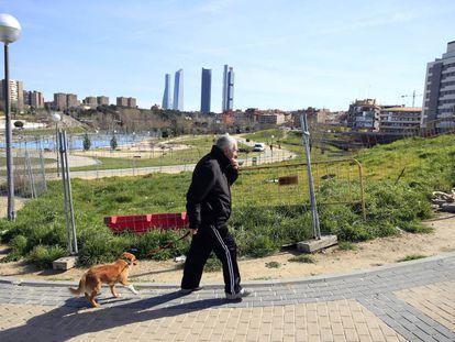 Un hombre pasea con su perro por el vallado parque Agustín Rodríguez Sahagún de Madrid.
