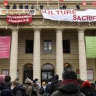 Demonstrators gather as members of the performing art branch of the French national trade union  General Confederation of Labour (Confederation Generale du Travail - CGT) hang banners and flags from the balcony of the French Theatre Odeon theatre de l'Europe, in Paris, on March 5, 2021 to ask for the reopening of cultural places, a year after the first closing measures to curb the spread of the Covid-19 pandemic. (Photo by Bertrand GUAY / AFP)
