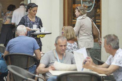 Una camarera sirve una mesa en una cafetería cétrica de Sevilla
