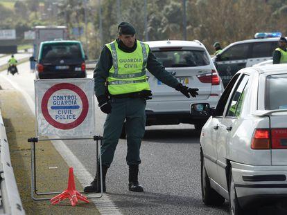Un guardia civil para un coche en la frontera entre Tui y Valenca, este lunes.