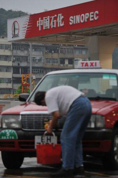 Un taxista lava su coche en una gasolinera de Sinopec en Hong Kong.