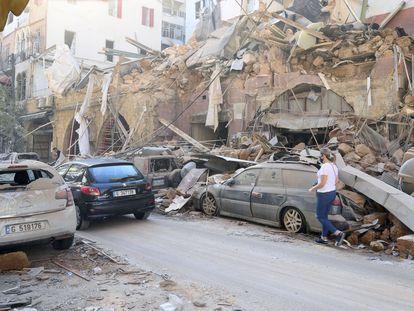Una mujer camina este miércoles junto a edificios y vehículos dañados por la deflagración del martes en Beirut.