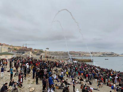 Cientos de personas esperan en la playa de la localidad de Fnideq (antiguo Castillejos) para cruzar los espigones de Ceuta este martes.