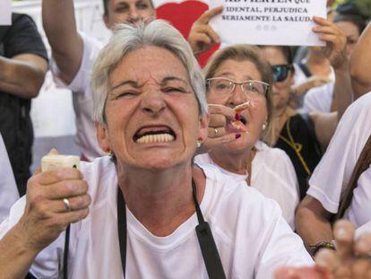 Una afectada por el cierre de las clínicas iDental muestra el estado de su boca durante la concentración de este miércoles / En vídeo, los afectados de Idental, en Madrid, recibirán en septiembre sus historias clínicas