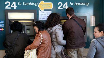 Varias personas se agolpan ante un cajero de Nicosia (Chipre).