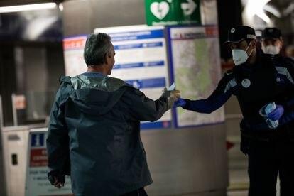 Agentes de la Policía Municipal de Madrid reparten mascarillas a los viajeros en la estación de metro de Sol, este lunes.