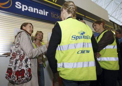 Varios trabajadores de Spanair conversan junto a la oficina de atención al cliente de la compañía en el aeropuerto de Gran Canaria.