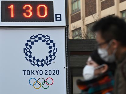 Ciudadanos de Yokohama pasan ante un cartel recordando que faltan 130 días para Tokio 2020.