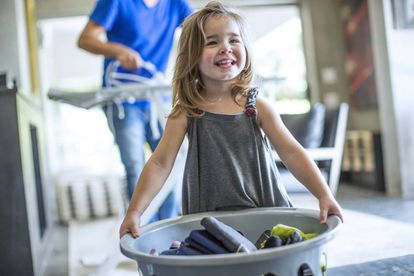 Una niña ayuda a su padre con la colada.