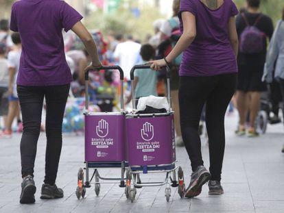 Dos mujeres participan en la campaña informativa contra la violencia sexista en las fiestas de San Sebastian.