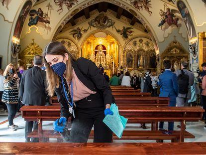 Una joven desinfecta los bancos de la Iglesia de Santa Genoveva, en Sevilla.