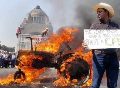 Un agricultor mexicano muestra una pancarta mientras arde un tractor a su espalda, en las protestas en México.