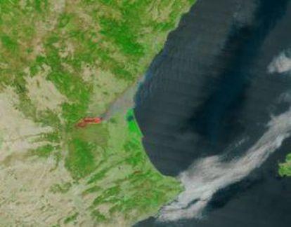 Imagen del fuego a mediodía del viernes tomada por el satélite Terra, de la NASA, y difundida por Oratge RTVV. Se aprecia la columna de humo que parte de la zona en llamas.