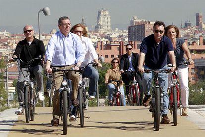 Gallardón da un paseo con su equipo en bicicleta eléctrica por el río.