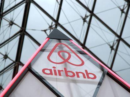 El logo de Airbnb al lado de la pirámide del museo Louvre de París, Francia.