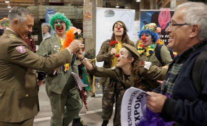 Una payasa le entrega una flor a un militar durante el acto de protesta pidiendo la desmilitarización de Expojove, la feria en Valencia destinada a niños y familias durante las vacaciones de Navidad.