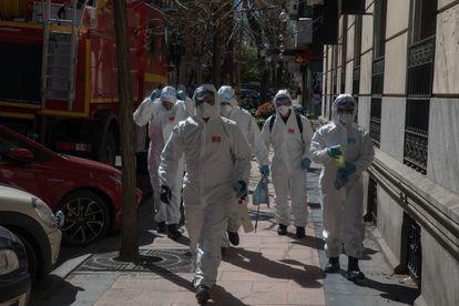 Los profesionales en trajes de protección. Miembros de la Unidad Militar de Emergencias (UME) se preparan para entrar a realizar labores de desinfección en el Hogar de Ancianos de las Hermanitas de los Desamparados, en Madrid.