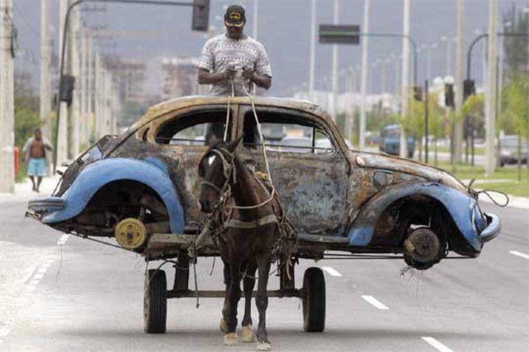 Un hombre traslada los restos de un coche quemado y abandonado en Río de Janeiro.