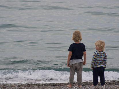 Dos niños observan el horizonte.
