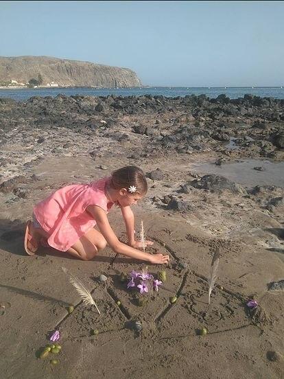 Una niña hace su mandala en la playa con piedras, plumas y flores dibujadas en El Médano.