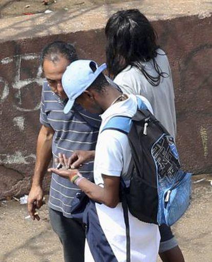 Usuários cuentan piedras de crack en la calle.