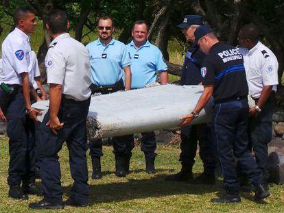 Policías y gendarmes transportan el alerón hallado en Reunión.