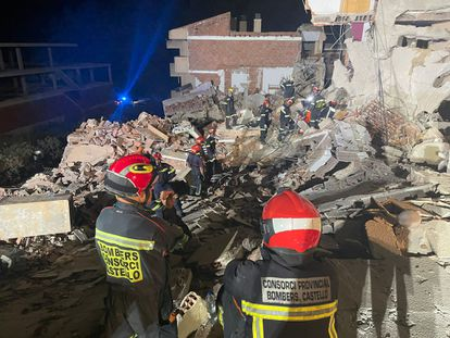 Los bomberos, entre los escombros del edificio.