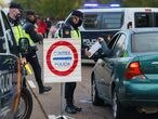 Policemen control a car at a checkpoint at the entrance of Leon,  northern Spain, on October 7, 2020, on the first day of a two week lockdown in an attempt to limit the contagion of the new coronavirus in the area. (Photo by CESAR MANSO / AFP)