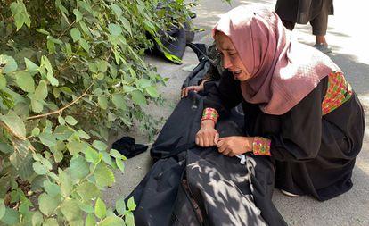 Una mujer llora en el exterior de un hospital de Kabul junto al cadáver de una víctima del atentado.