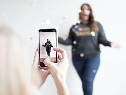 Dos jóvenes graban un video con su móvil.