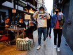 People wearing protective masks walk past bar customers after bars reopened in Spain's Basque Country, amid the coronavirus disease (COVID-19) outbreak, in Bilbao, Spain, February 19, 2021. REUTERS/Vincent West