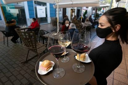Una camarera se dispone a servir en una terraza de un restaurante de Avilés (Asturias) el pasado lunes.