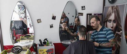 Un barbero afeita a un joven en una peluquería de Atenas el pasado viernes.