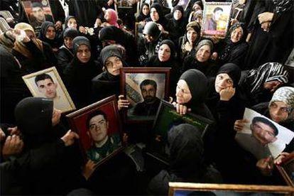 Mujeres libanesas portan retratos de sus familiares muertos durante la guerra, en una ceremonia fúnebre en la localidad sureña de Srifa.