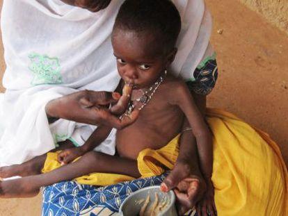 Una mujer alimenta a su hijo con pasta de cacahuete.