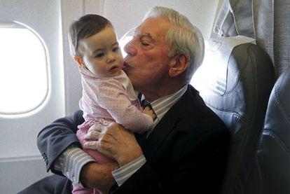 Mario Vargas Llosa, fotografiado ayer con su nieta en brazos en el avión que le llevó a Estocolmo, donde el viernes recibirá el Nobel.