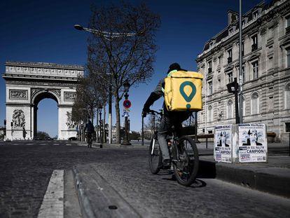 Un repartidor atraviesa unos Campos Elíseos casi vacíos, en París.