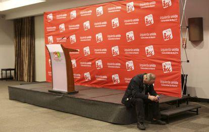 Francisco Frutos consulta su móvil mientras sigue el escrutinio en la sede de IU, en la noche electoral del pasado 24 de mayo.