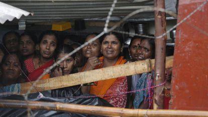 Varias mujeres se protegen de la lluvia bajo un tejado mientras observan las labores de rescate tras derrumbarse un muro en Bombay (India), este martes. Al menos 15 personas han muerto tras el siniestro provocado por las fuertes precipitaciones que ha traído este año el monzón.