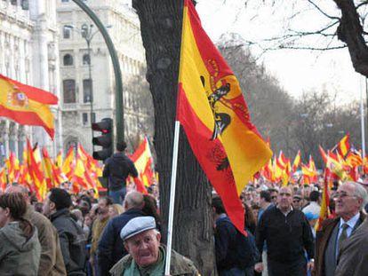 Un anciano acompaña la manifestación del PP contra la política antiterrorista del Gobierno sujetando una bandera del régimen franquista.