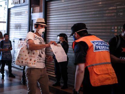 Un hombre le muestra a la policía un certificado para poder circular libremente en Buenos Aires.