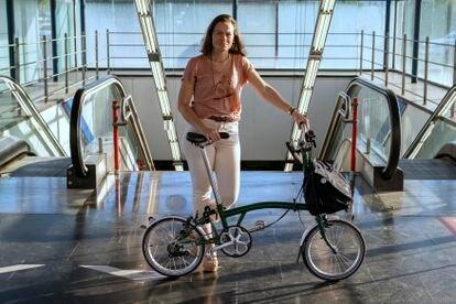 Isabel Ramis posa con su bici plegable en la entrada de una estación de metro de Madrid.