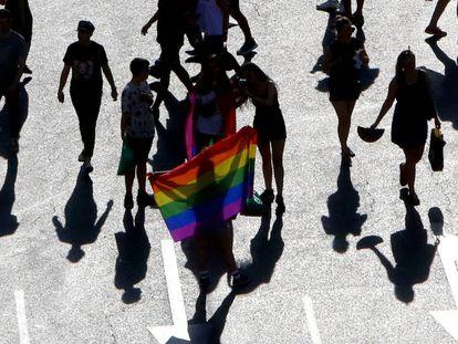 Varias personas sostienen una bandera arcoiris en el desfile del Día del Orgullo Gay en julio de 2018 en Madrid.