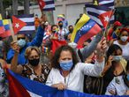 """People in Caracas demonstrate in support of the Cuban government and their supporters, outside the Cuban embassy in the Venezuelan capital on July 12, 2021. - Thousands of Cubans took part in rare protests Sunday against the communist government, chanting """"Down with the dictatorship"""" as President Miguel Diaz-Canel called on his supporters to confront the demonstrators. The anti-government rallies started spontaneously in several cities as the country endures its worst economic crisis in 30 years, with chronic shortages of electricity and food. (Photo by Federico PARRA / AFP)"""