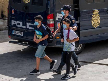 Un policía nacional acompaña a dos menores, el pasado 20 de mayo, en Ceuta.