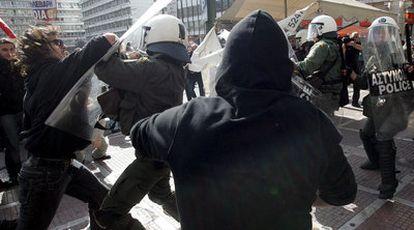 Enfrentamiento entre la policía y un grupo de manifestantes al término de la marcha de protesta que ayer recorrió Atenas.
