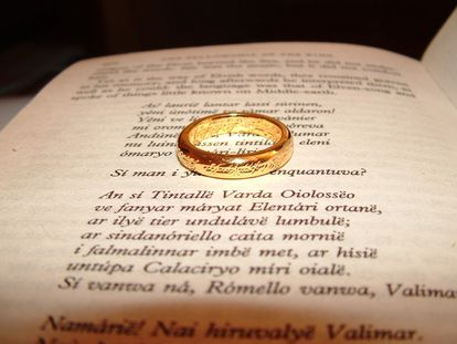 Una página del libro 'La comunidad del anillo' en lengua élfica, junto con una réplica del Anillo Único.