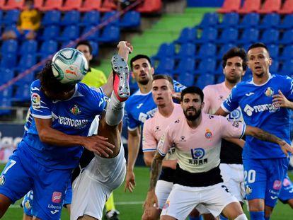 Olivera cabecea un balón ante la defensa del Espanyol.
