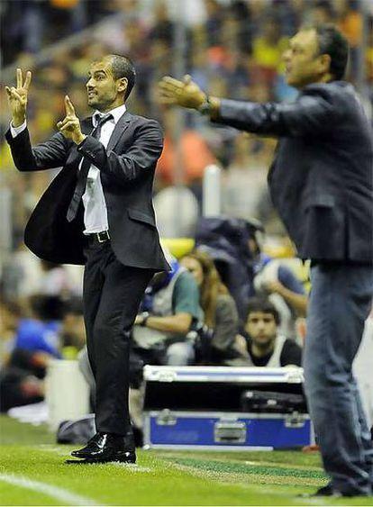 Pep Guardiola, al fondo, junto a Joaquín Caparrós, en el partido de ida de la Supercopa de España.